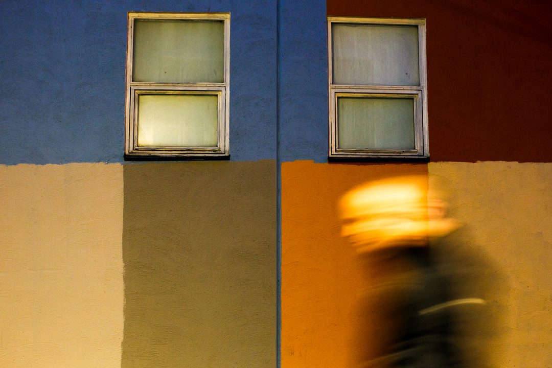 Bold Man in Motion in front of multicoloured wall with two white windows
