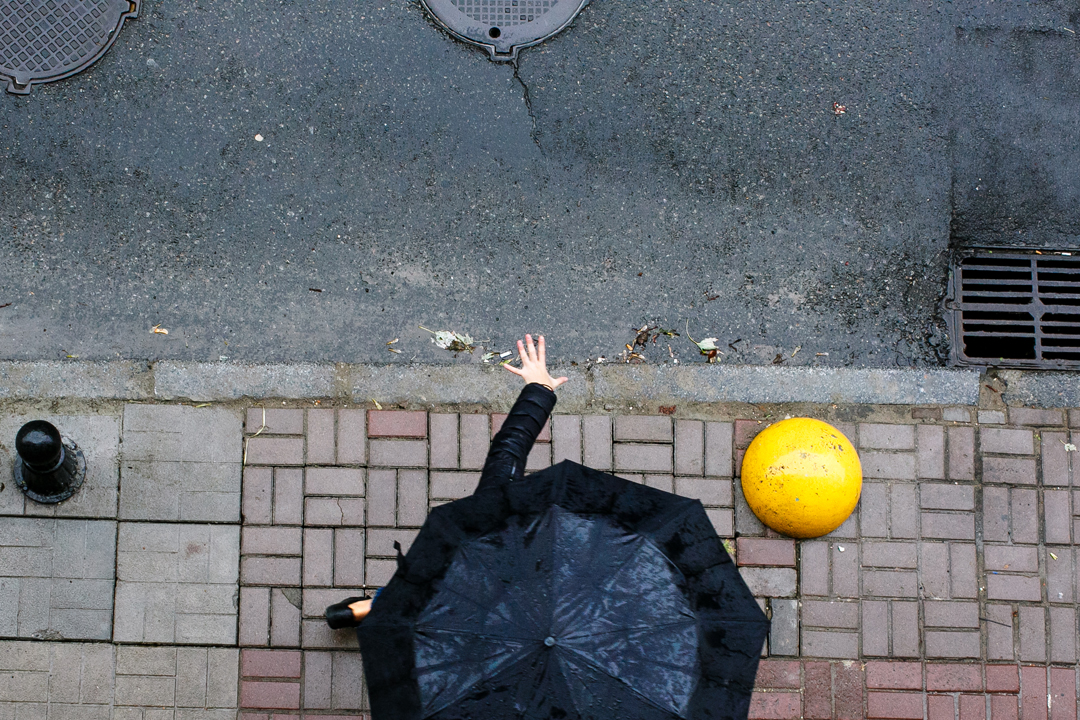 Left Hand out of Black Umbrella in Rain