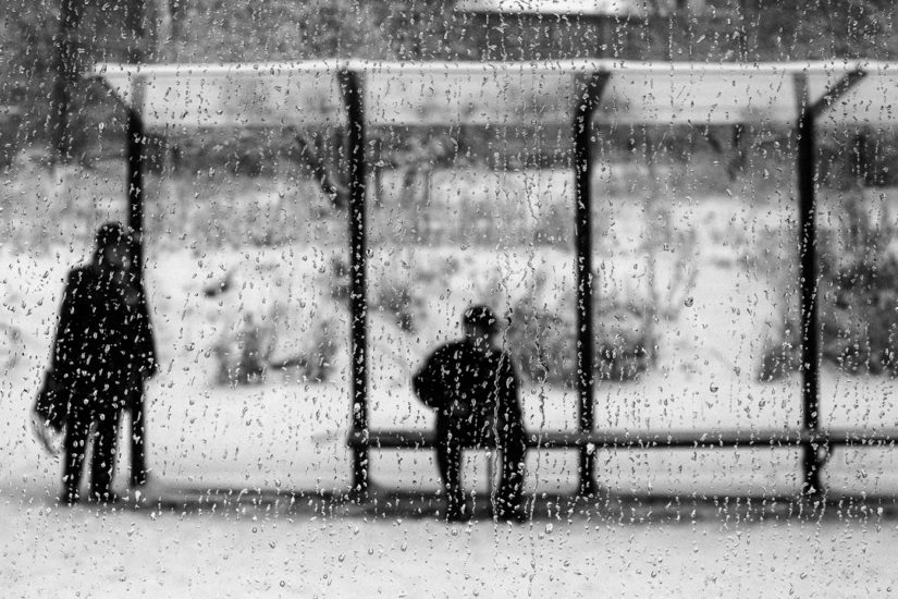 Man Sitting on the Tram Station and Woman Staying nearby through the glass of Snowy Tram with Rain Drops